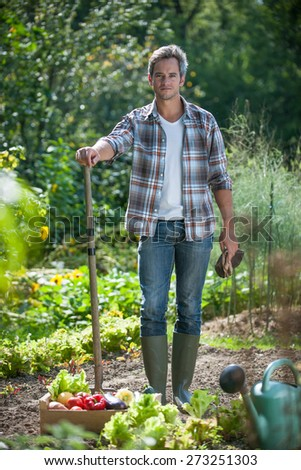 looking at camera, gardener standing in his garden, crate filled with vegetables at his feet