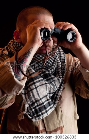 Looking for enemy: mercenary with binoculars