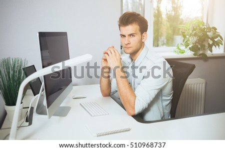 Looking from the working men in the office. Stylish designer at work sitting at a desk. Focused on his job businessman looking at camera. White interior