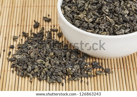 loose leaf gunpowder green tea in a white china cup and spilled over bamboo mat
