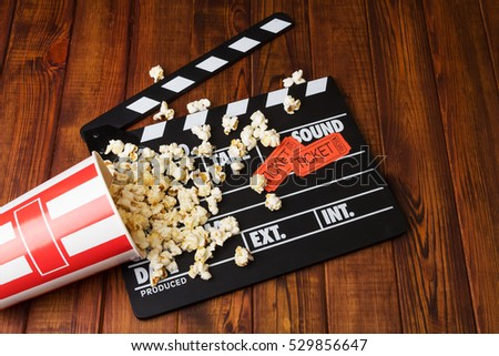 Loose popcorn, striped box, movie tickets and movie clapper on a wooden background