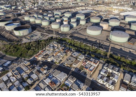 Los Angeles County, California, USA - December 17, 2016:  Middle class homes below large oil refinery tanks in Southern California.