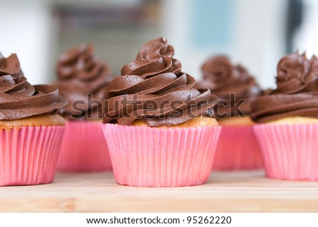 lots of chocolate frosted cupcakes in pink wrappers