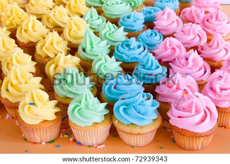 lots of rainbow cupcakes with sprinkles