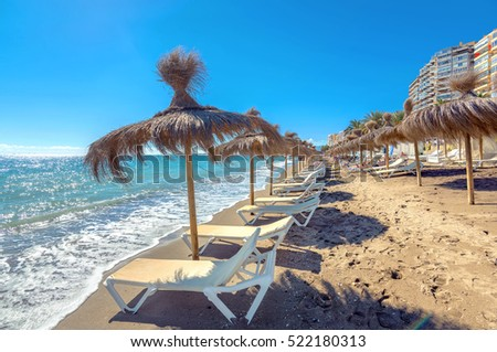 Lounge chairs and straw umbrellas at the beach in Malaga. Costa del Sol, Andalusia, Spain