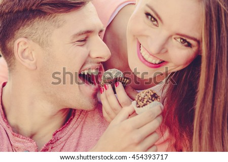 Love and happiness. Cute lovely lovers feeding each other by cupcakes cookies. Smiling couple with sweet food having fun.