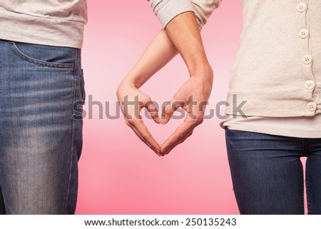 love and relationships concept -  woman and man hands showing heart shape