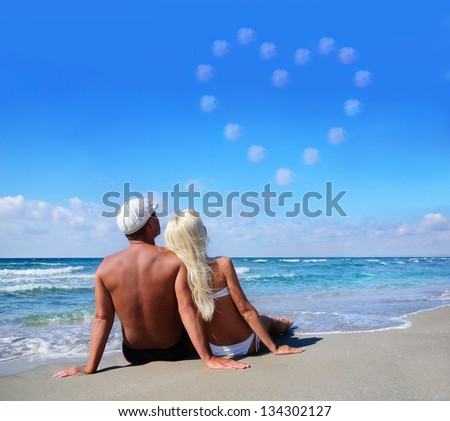 love concept - young couple on sea sand beach look at sky cloudy heart