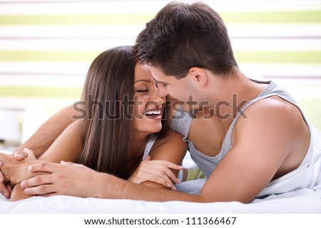 Love couple lying in bed kissing and looking each other