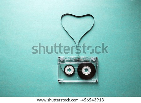 love for music, twisted audio tape in the shape of a heart on a green background