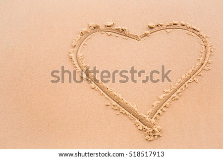 Love heart drawn on wet sand by the waves on the shore. Background.