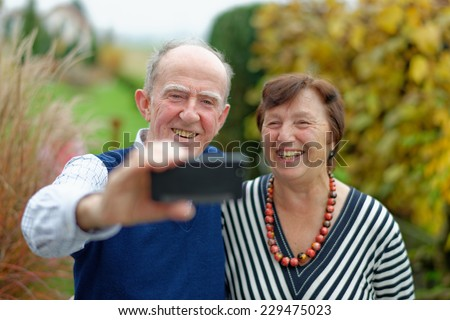Love in focus. Happy senior couple bonding to each other and making selfie while standing outdoors