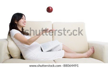 Lovely asian pregnant woman throwing an apple upward
