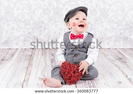 lovely baby boy in barret with lipstick kiss on his cheek and red heart
