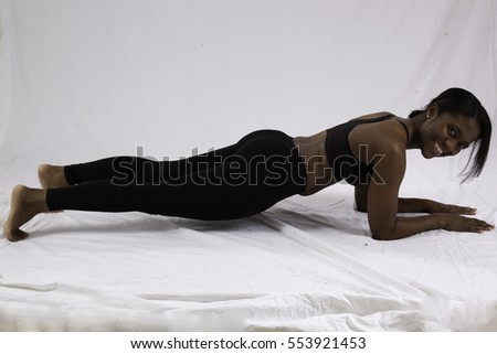 Lovely black woman in exercise wear, Planking  and  smiling at the camera
