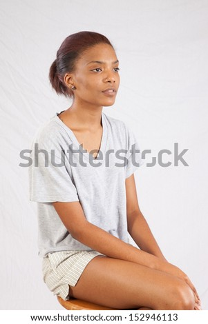 Lovely black woman sitting   with a friendly, thoughtful, expression