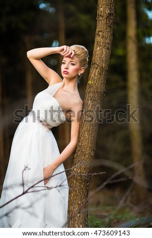 Lovely bride on her wedding day outdoors in a forest (color toned image; shallow DOF)