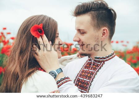 Lovely couple  in the poppy field. Ukrainian traditional clothes