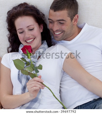 Lovely couple on sofa, woman holding a rose