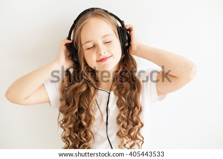 Lovely little girl in headphones enjoy with a music