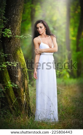 Lovely young lady wearing an elegant long white dress enjoying the beams of celestial light on her face in enchanted woods. Long hair brunette woman looking as a glamorous princess in the forest