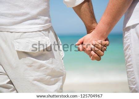 Loving couple holding hands at the beach