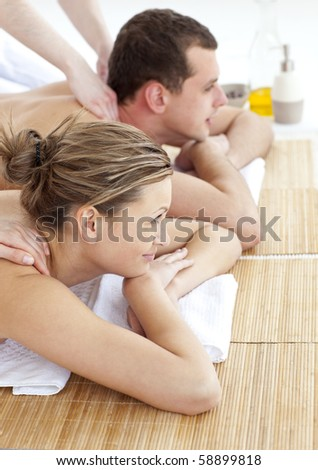 Loving couple receiving a back massage in a spa center