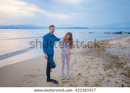 Loving couple running along the beach. Cheerful couple. Love. Sunset. Sea shore. Relations.