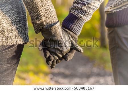 Loving couple wearing gloves holding each other by hands and walking in the park on sunset light . Focus point on the woman's hand. Close up.