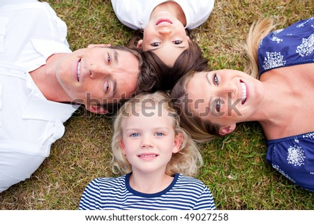 Loving family lying in circle on the grass in a park