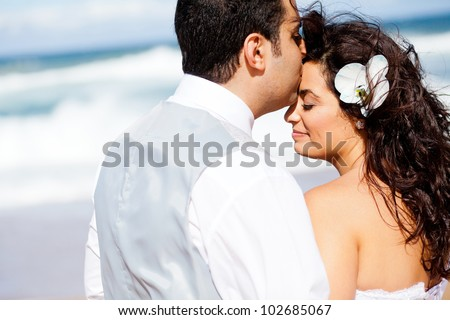 loving groom kissing bride's forehead on beach