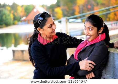 Loving mother and daughter talking to each other in outdoors