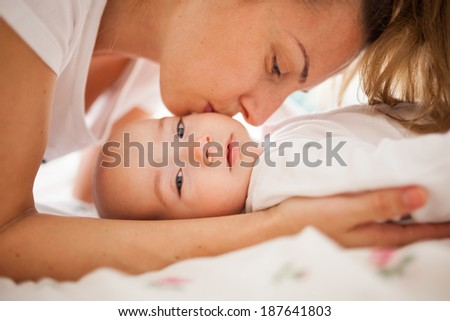 Loving mother kissing her baby boy's cheek