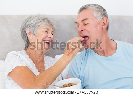 Loving senior woman feeding cereals to husband at home