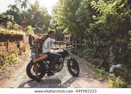 Loving young couple on a motorcycle. Young man and woman on motorbike in a village on a summer day.