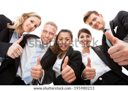 Low angle portrait of business people gesturing thumbs up against white background