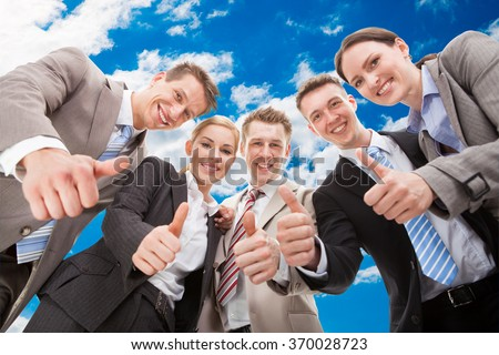 Low angle portrait of confident business team showing thumbs up against sky