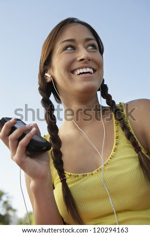 Low angle view of a beautiful woman listening to music against sky