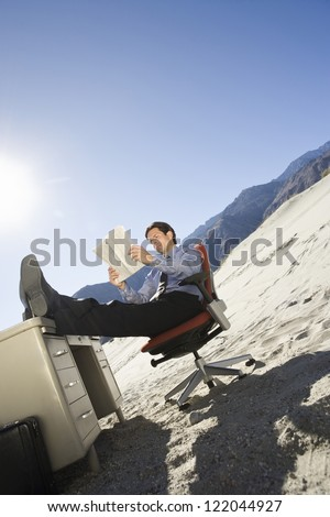 Low angle view of a businessman reading magazine while sitting on desert against sky