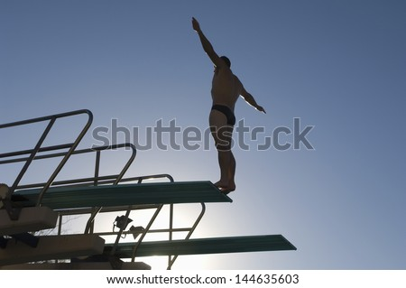 Low angle view of a male diver with arms out about to dive against the blue sky