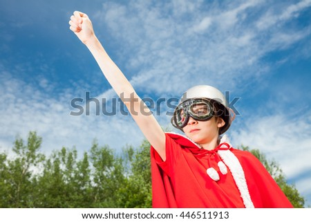 Low angle view of cute teen boy wearing metal cauldron as a helmet goggles and red costume - a funny power super hero child concept