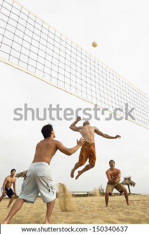Low angle view of young male friends playing volleyball on beach