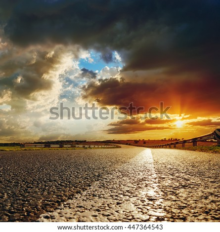 low orange sunset in dramatic clouds over asphalt road