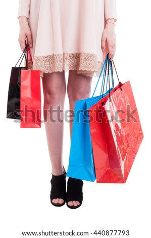 Low section of young stylish girl carrying colorful shopping bags as fashion and consumerism concept isolated on white background