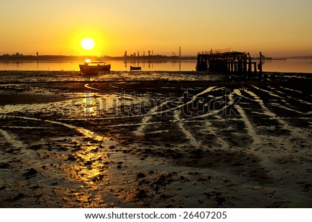 Low tide in a beach with boats and old pier at sunset