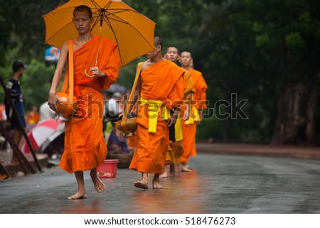 Luang Prabang, Laos - July 25, 2008 : Monk Alms Giving Procession. Every morning the main street of Luang Prabang, is lined with people kneeling and offering alms to the procession of local monks.