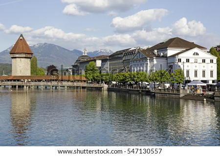 LUCERNE, SWITZERLAND - MAY 04, 2016: Roofed Chapel Bridge and octagonal tower these are most recognizable landmarks in the city. On the banks of the river Reuss the theater building can be seen