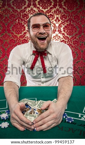 Lucky Blackjack winner man with glasses on and Texas Tie. He is at a gambling table taking in his winnings.  A huge smile is on his face