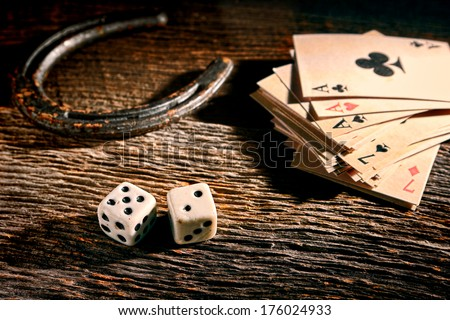 Lucky craps game dice rolling out chance number seven and vintage poker cards with winning aces by old horseshoe for player and gambler good luck charm on rustic wood table in western gambling saloon