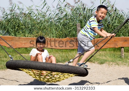 lucky siblings playing with a birds nest swing on a playground